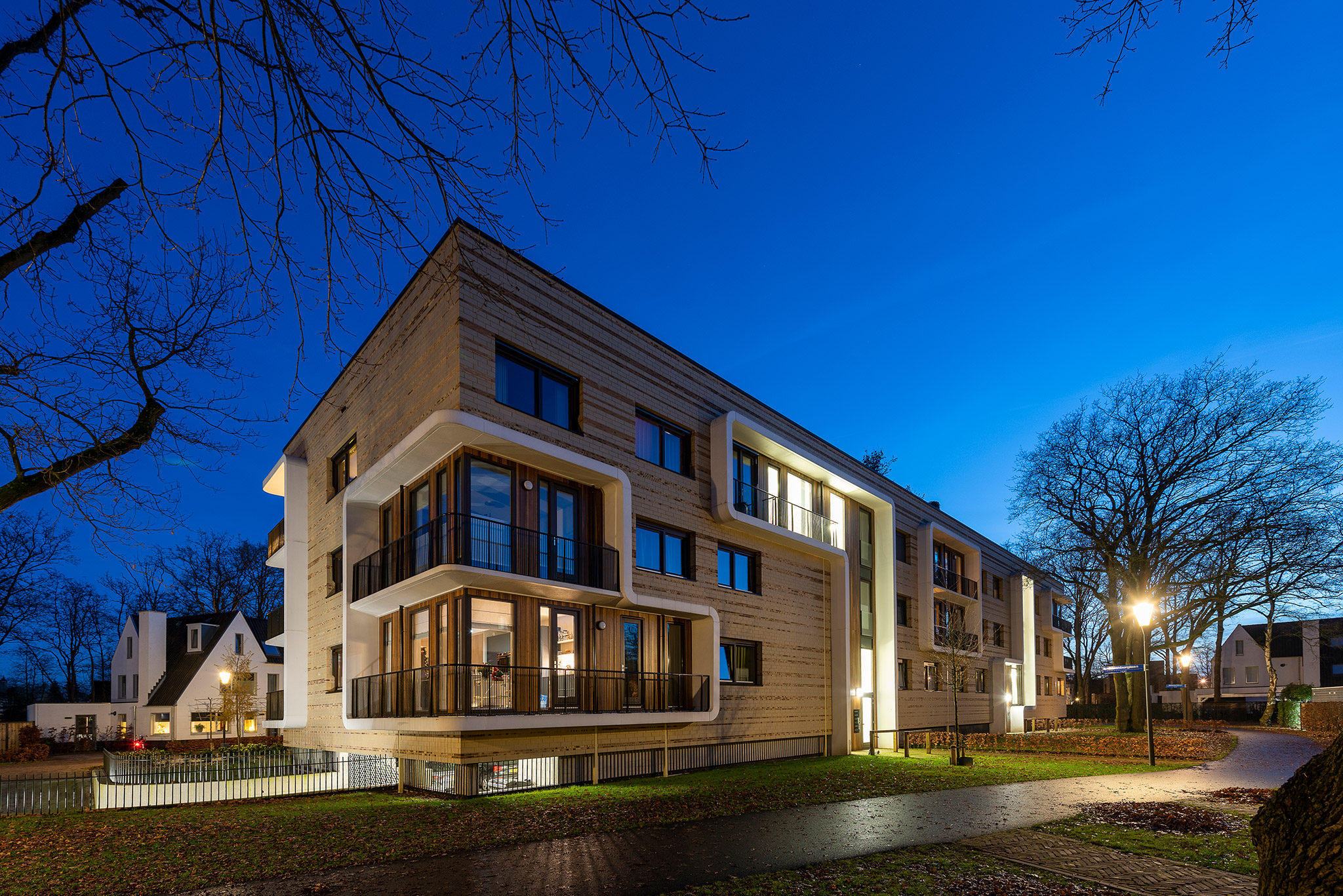Simone Drost Architecture Planet Pab Architecture Appartementen Stdhouderspark Vught voorgevel overzicht entreegevel en entree parkeergarage bij schemer